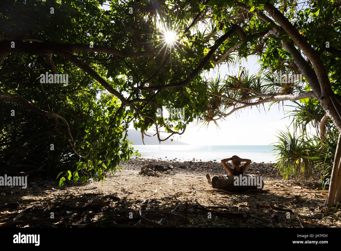 A person leans against a log and relaxes in the shade of a tree, out of the hot sun, on a beautiful tropical beach - Stock Image