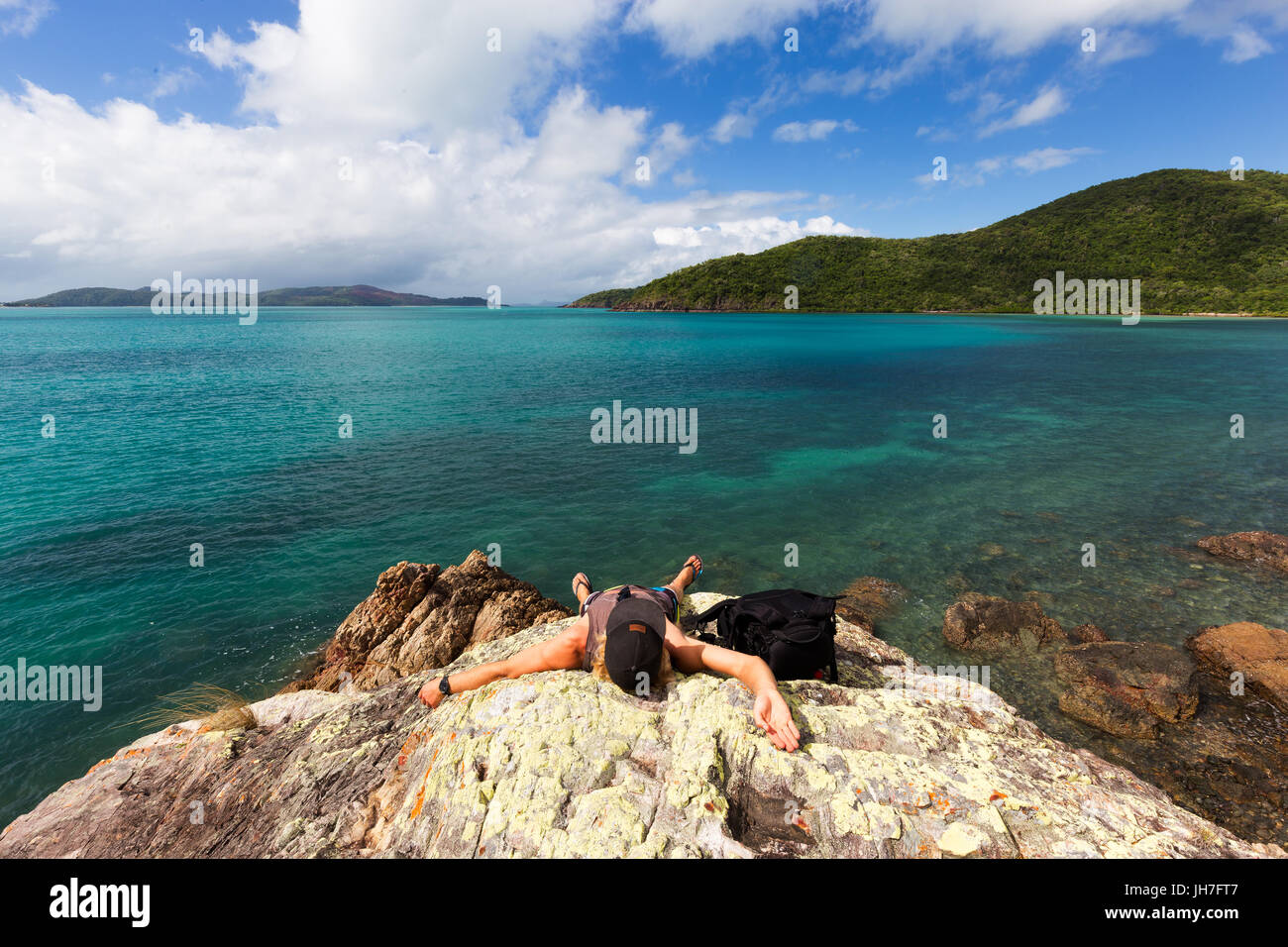 An exhausted traveler rests on a boulder at a beautiful isolated tropical beach in northern Queensland, Australia. - Stock Image