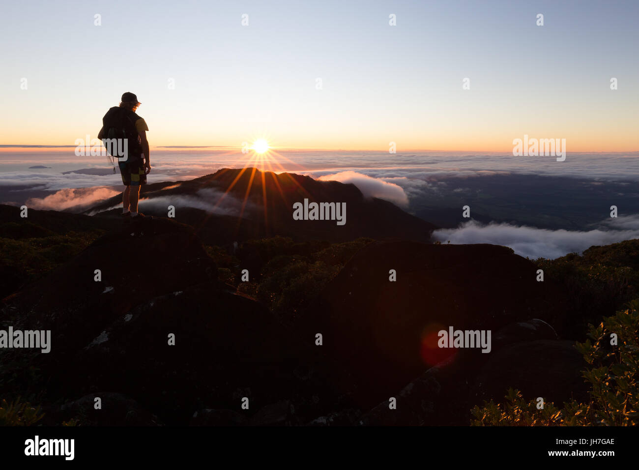 A hiker watches a beautiful sunrise on from the summit of a mountain above the clouds in Australia. Stock Photo