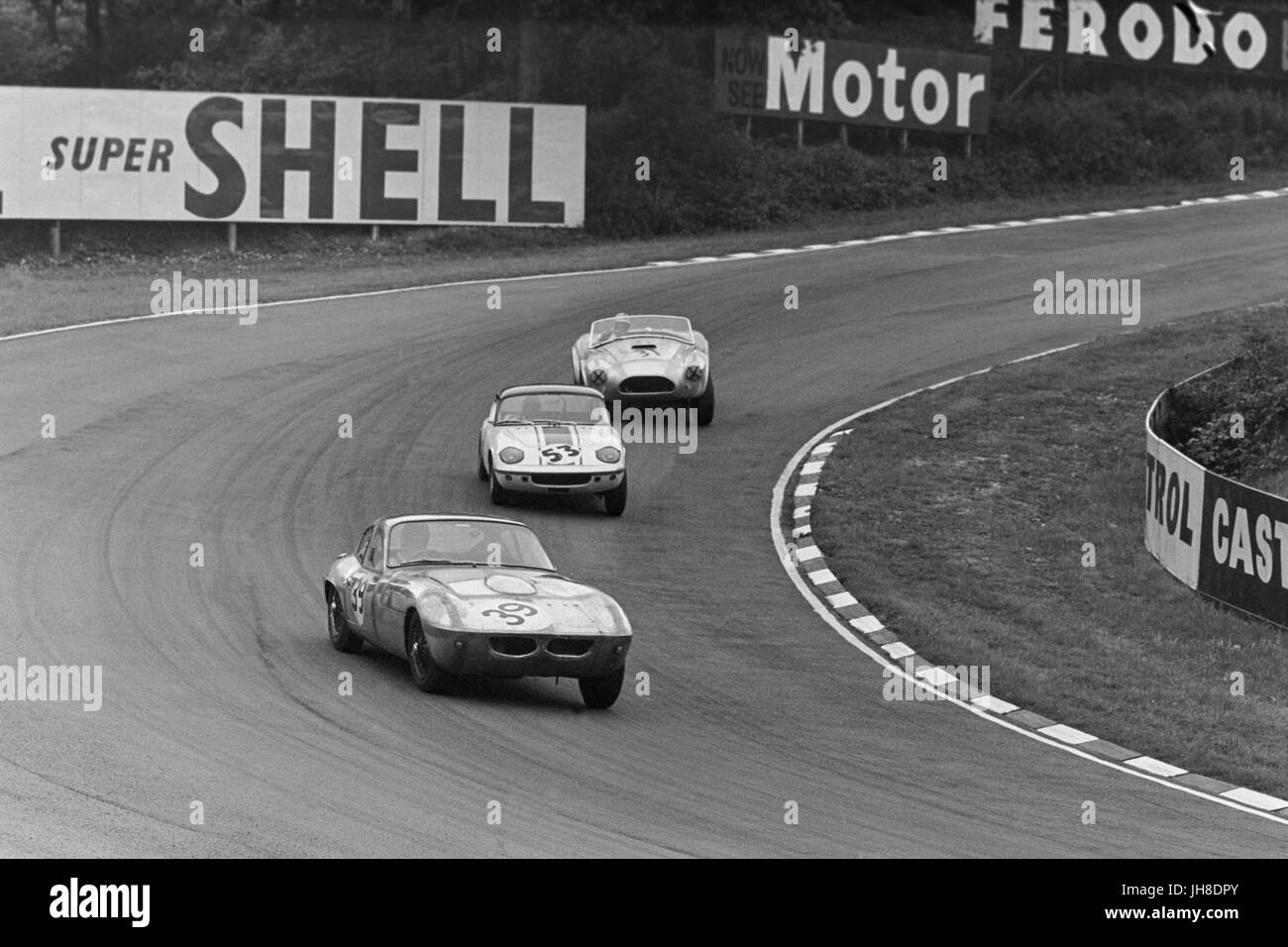 Racing at Brands Hatch in 1964. Gordon Spice in a Morgan Plus 4 SLR, leads Clive Hunt in a Lotus Elan, followed - Stock Image