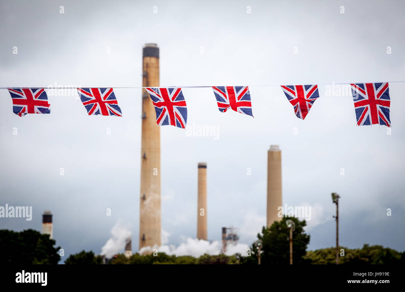 Refinery chimneys with Union Jack bunting flags in the foreground - Stock Image