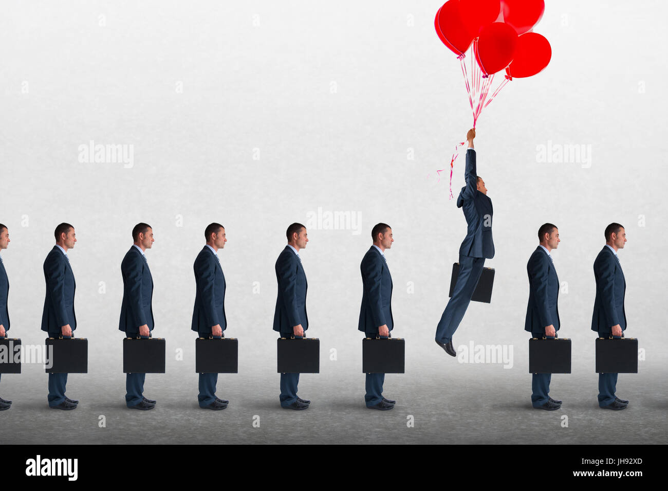 entrepreneurial business concept businessman rising above a queue of businessmen with helium balloons - Stock Image