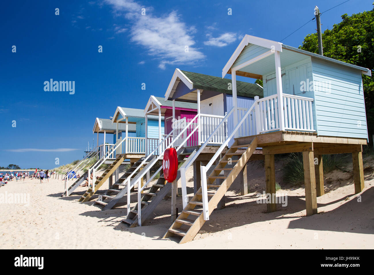 Rows of colourful beach huts on stilts on the sunny, sandy beach at Wells Next The Sea in Norfolk, UK which is a - Stock Image