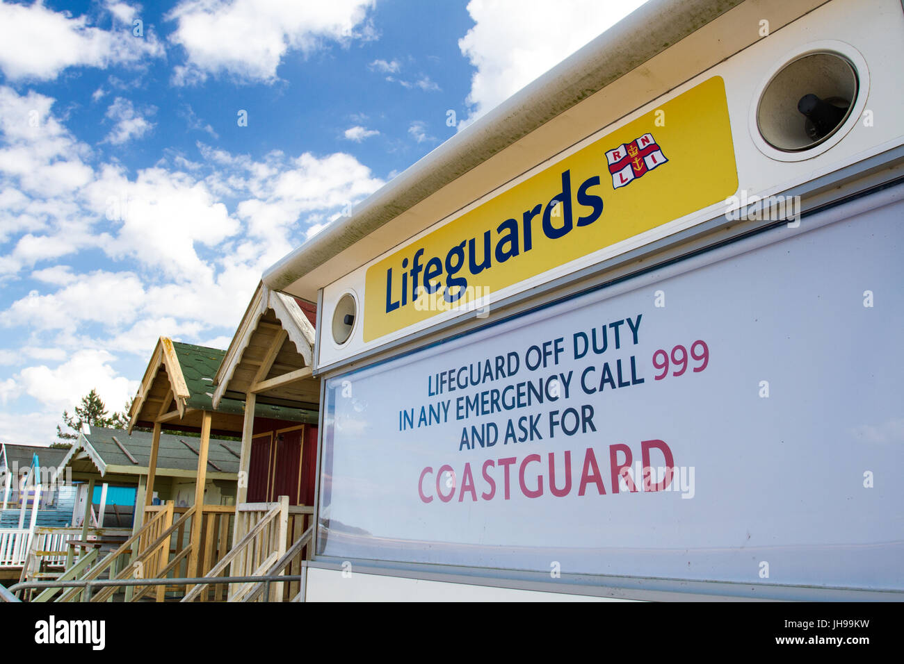 An HM Coastguard station and rows of beach huts on a sandy beach in Norfolk, UK that is closed representing a beach - Stock Image