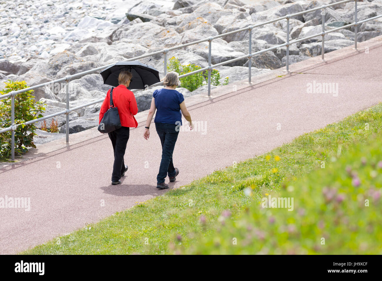 Two woman walking down the Wales Coastal Path at Rhos-on-Sea next to Colwyn Bay in North Wales on a hot day in summer - Stock Image