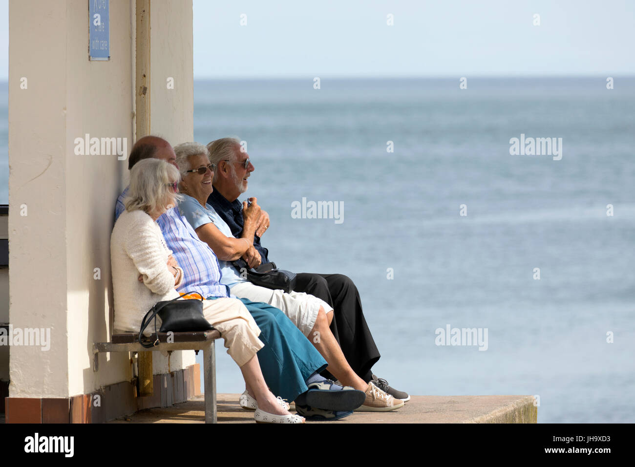 Elderly people sitting in the shade of a promenade shelter at the coatal resort town of Llandudno in North Wales - Stock Image