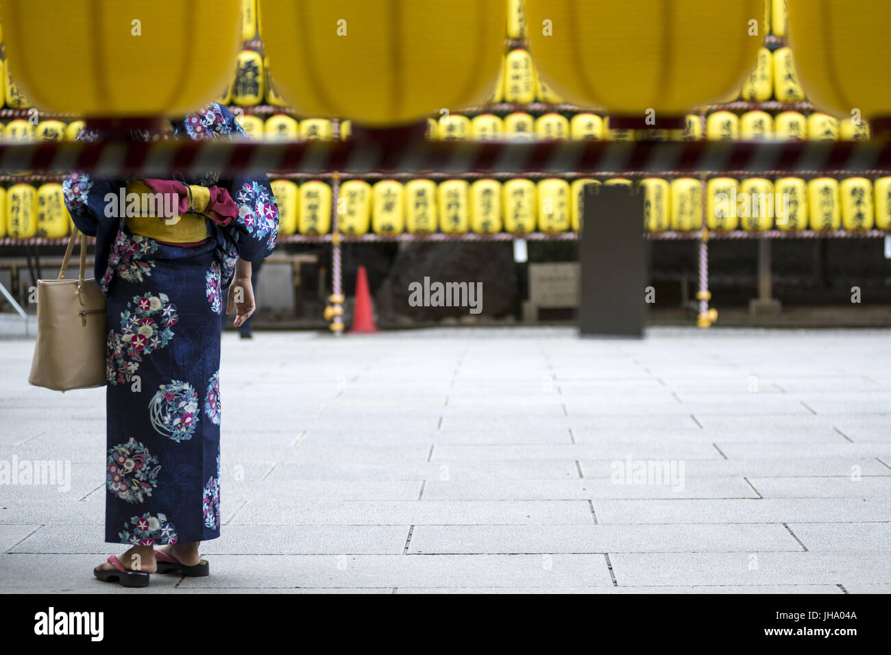 Hiratsuka, Kanagawa, Japan. 13th July, 2017. Women walk in front of a row of paper lanterns with the names of the - Stock Image