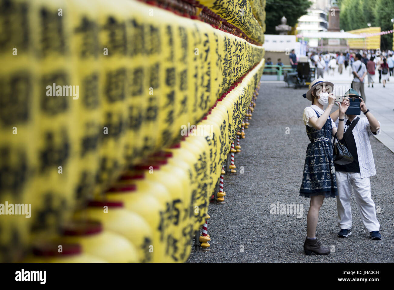 Hiratsuka, Kanagawa, Japan. 13th July, 2017. A visitors takes pictures of a row of paper lanterns with the names - Stock Image