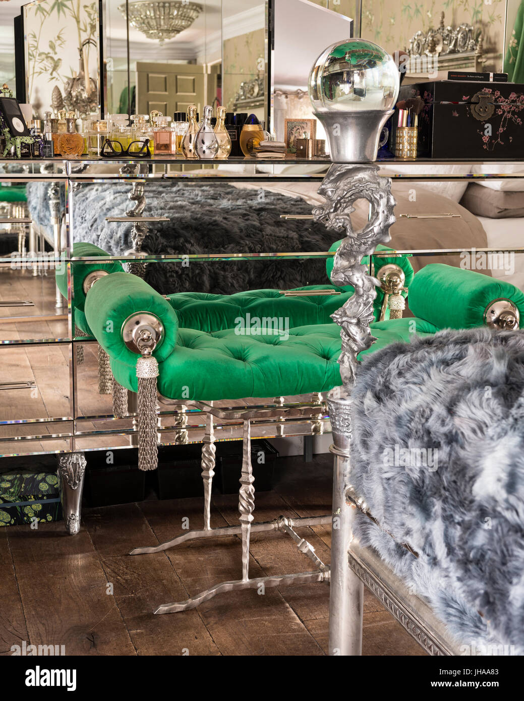 Green stool by mirrored drawers - Stock Image
