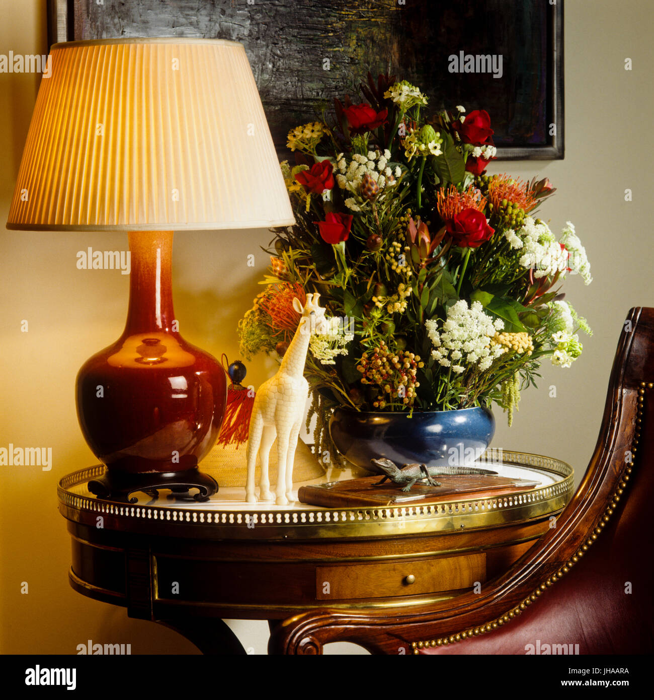 Lit lamp and flowers on table - Stock Image