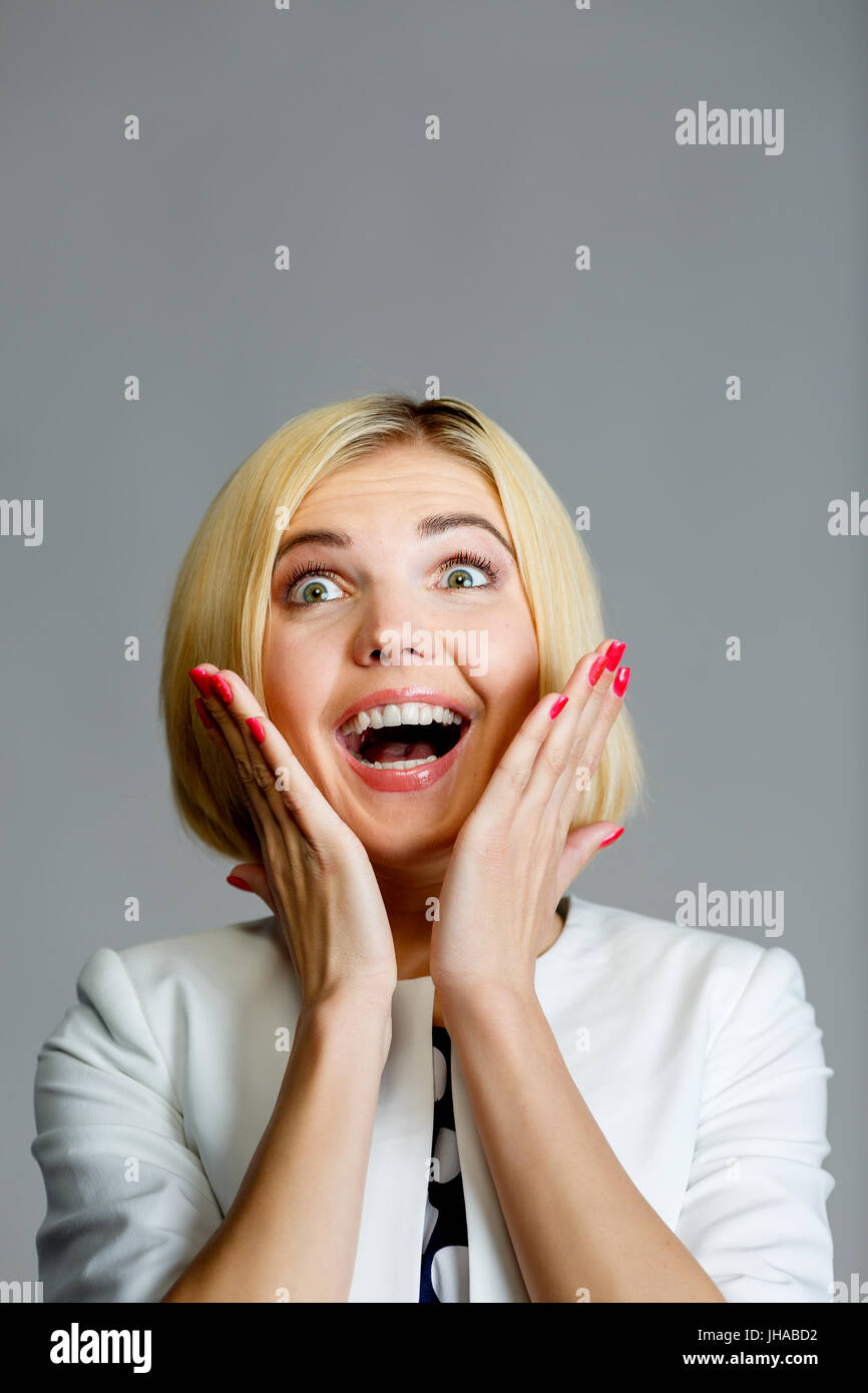Smiling woman with hands at face on empty gray background Stock Photo