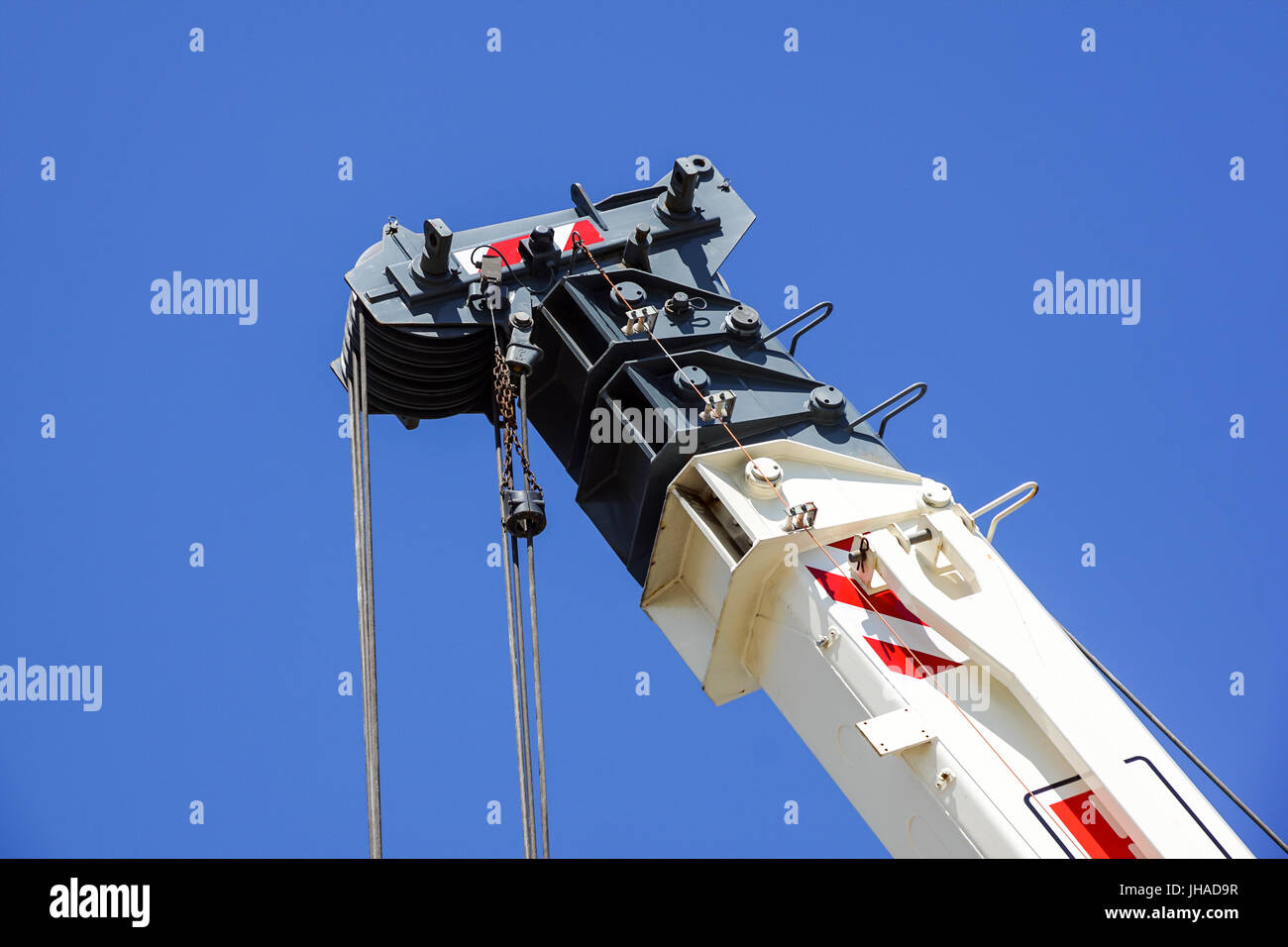 truck crane detail boom with hooks and scale weight above blue sky Stock Photo