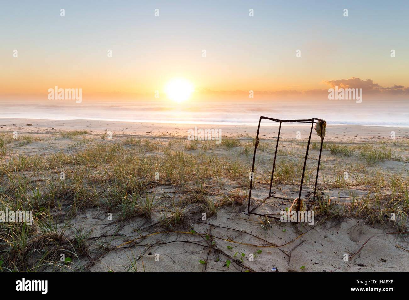 A rusted piece of rectangular ocean litter sits on the beach as the sunrise illuminates the beautiful coastline - Stock Image