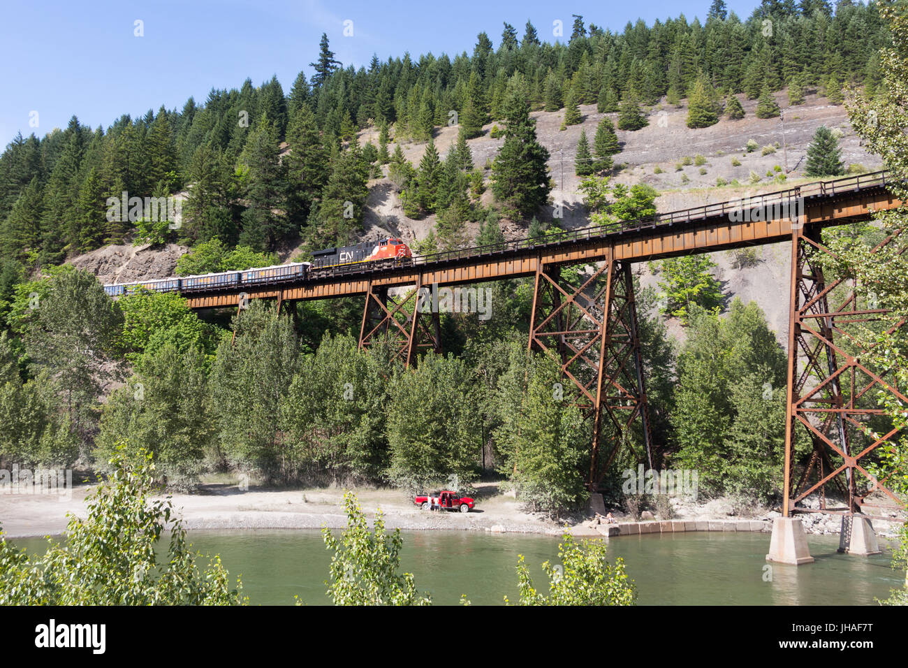 A train operated by CN Rail is crossing the Anderson Creek railway bridge in the Fraser Canyon near Boston Bar, - Stock Image