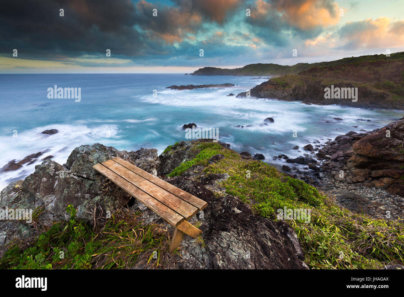 An empty wooden bench with a view over a beautiful rocky coastline at sunset in Australia. Stock Photo