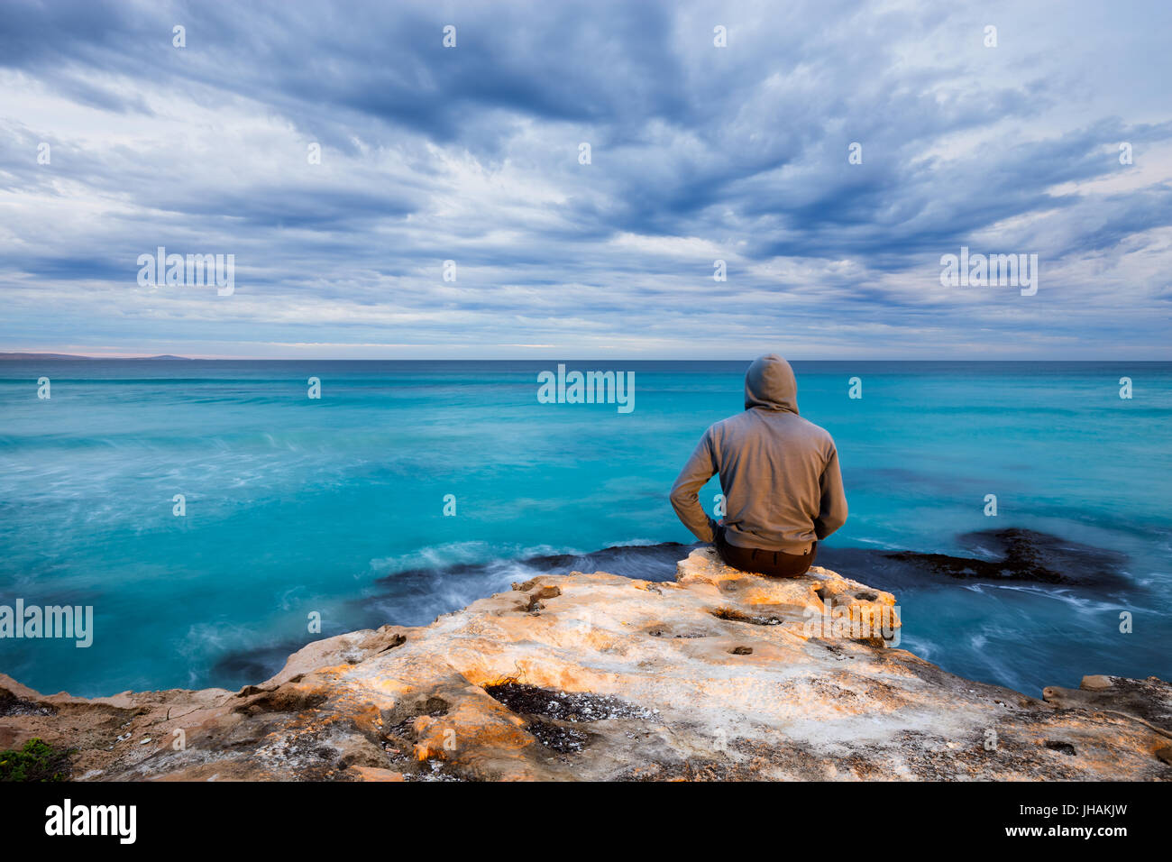 A man sits on the edge of a rugged limestone cliff and looks over a stormy ocean view in South Australia. - Stock Image