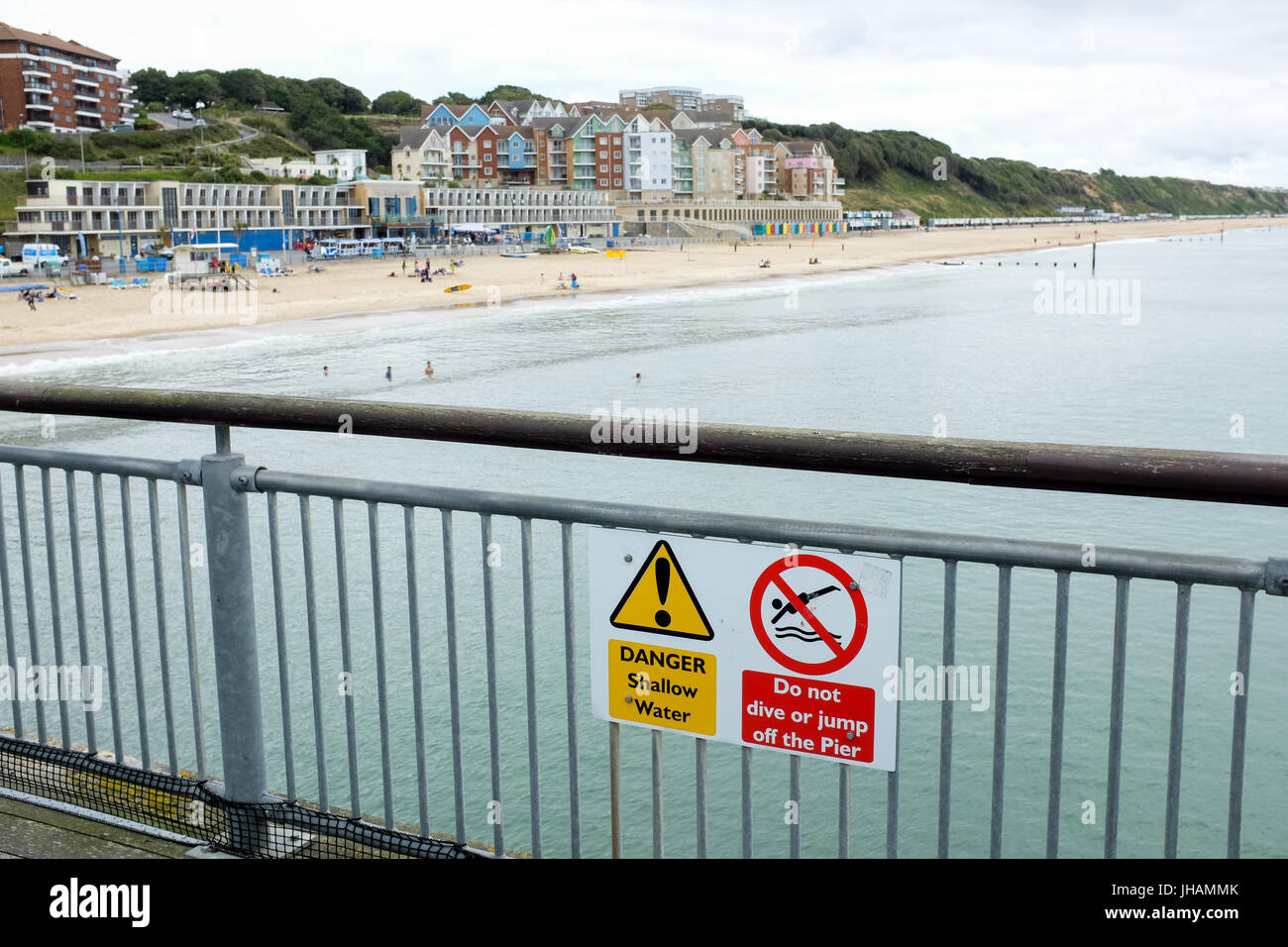 A sign warning people of shallow sea water and telling people not to dive or jump off the pier (Boscombe pier near - Stock Image