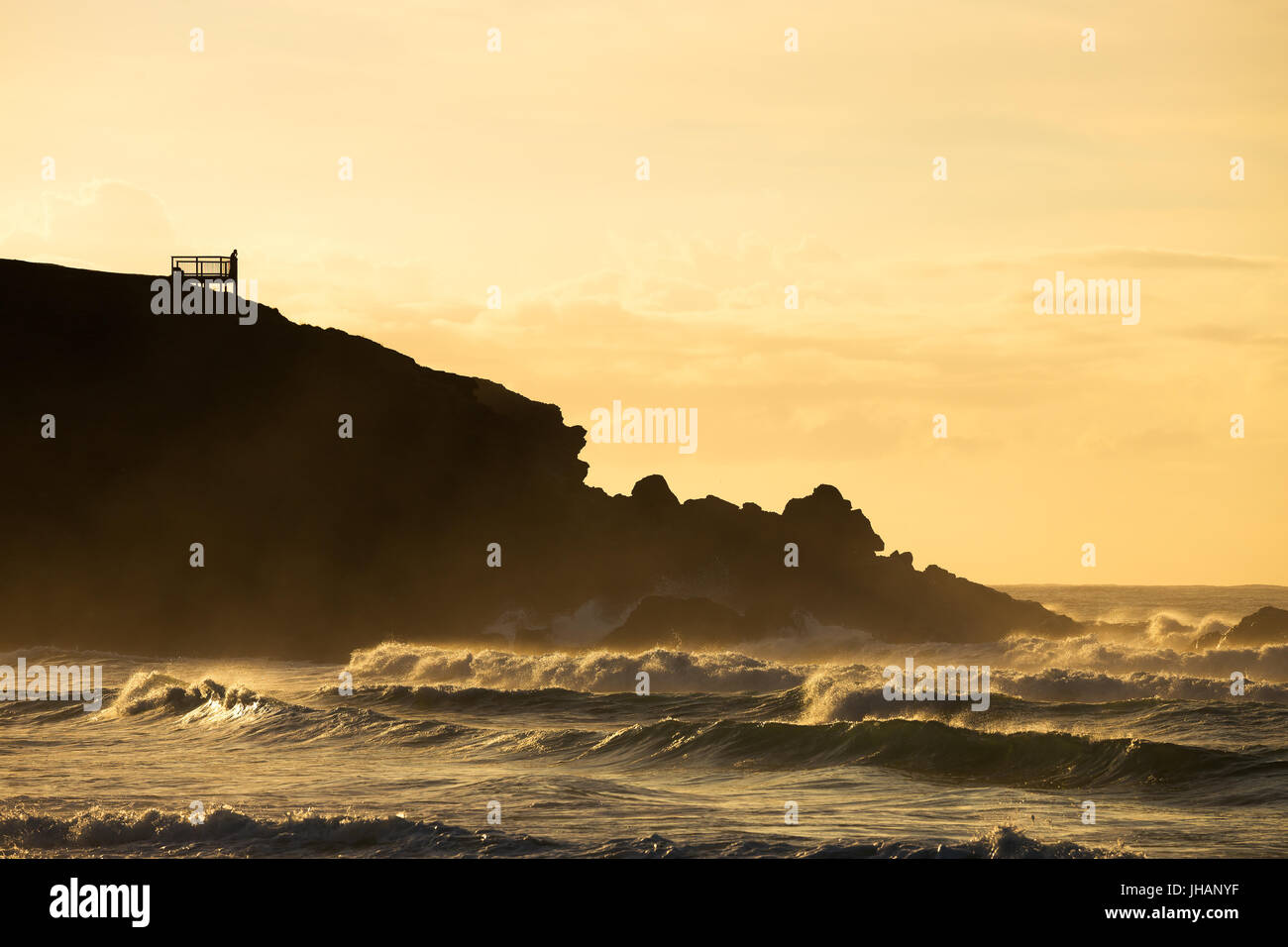 A silhouetted person watches the waves breaking on the beach in golden morning light from a viewing platform. Stock Photo