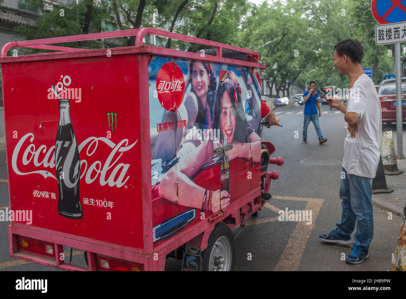 An electric tricycle features Coca-Cola celebrating the 100th birthday of its contour bottle in 2015 with a year - Stock Image