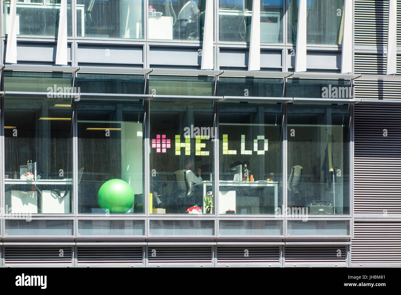 Office worker spells out 'hello' with post it notes on window, London, UK - Stock Image
