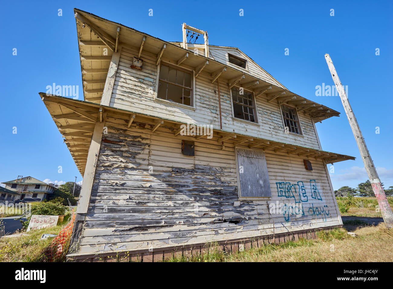 close-up of vacant decayed house with blown out windows - Stock Image
