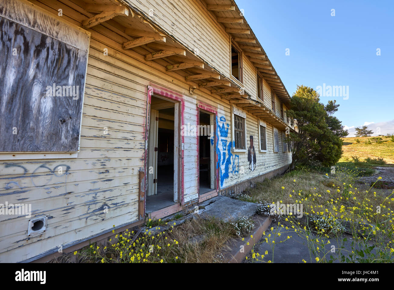 defunct and abandoned housing; long shot with glimpse of destroyed interior - Stock Image