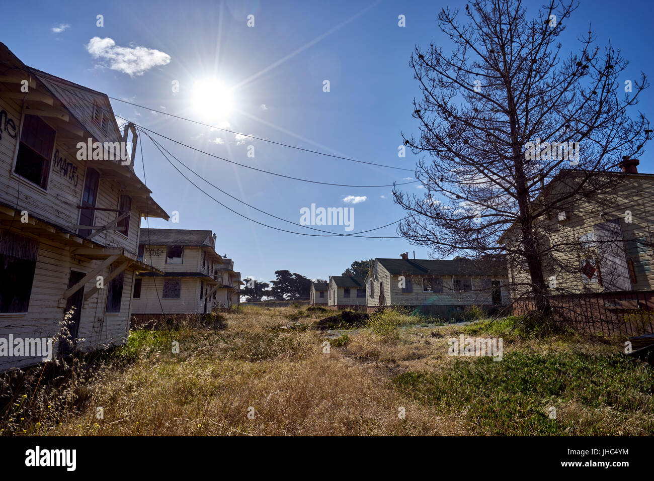 puffy white clouds over abandoned and deserted barracks - Stock Image