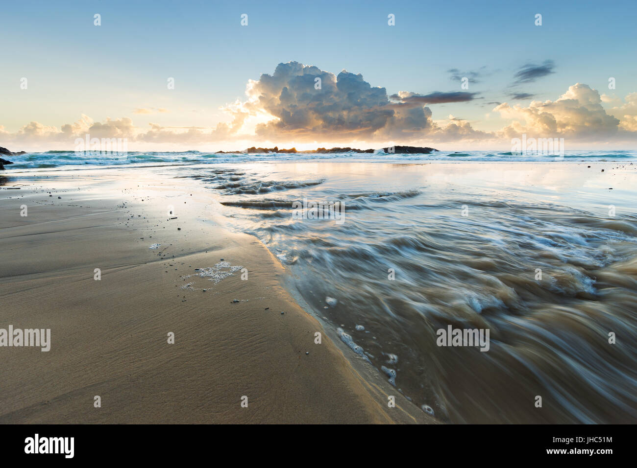 A fresh water stream flows into the sea on a beautiful empty beach in Australia as storm clouds are illuminated - Stock Image