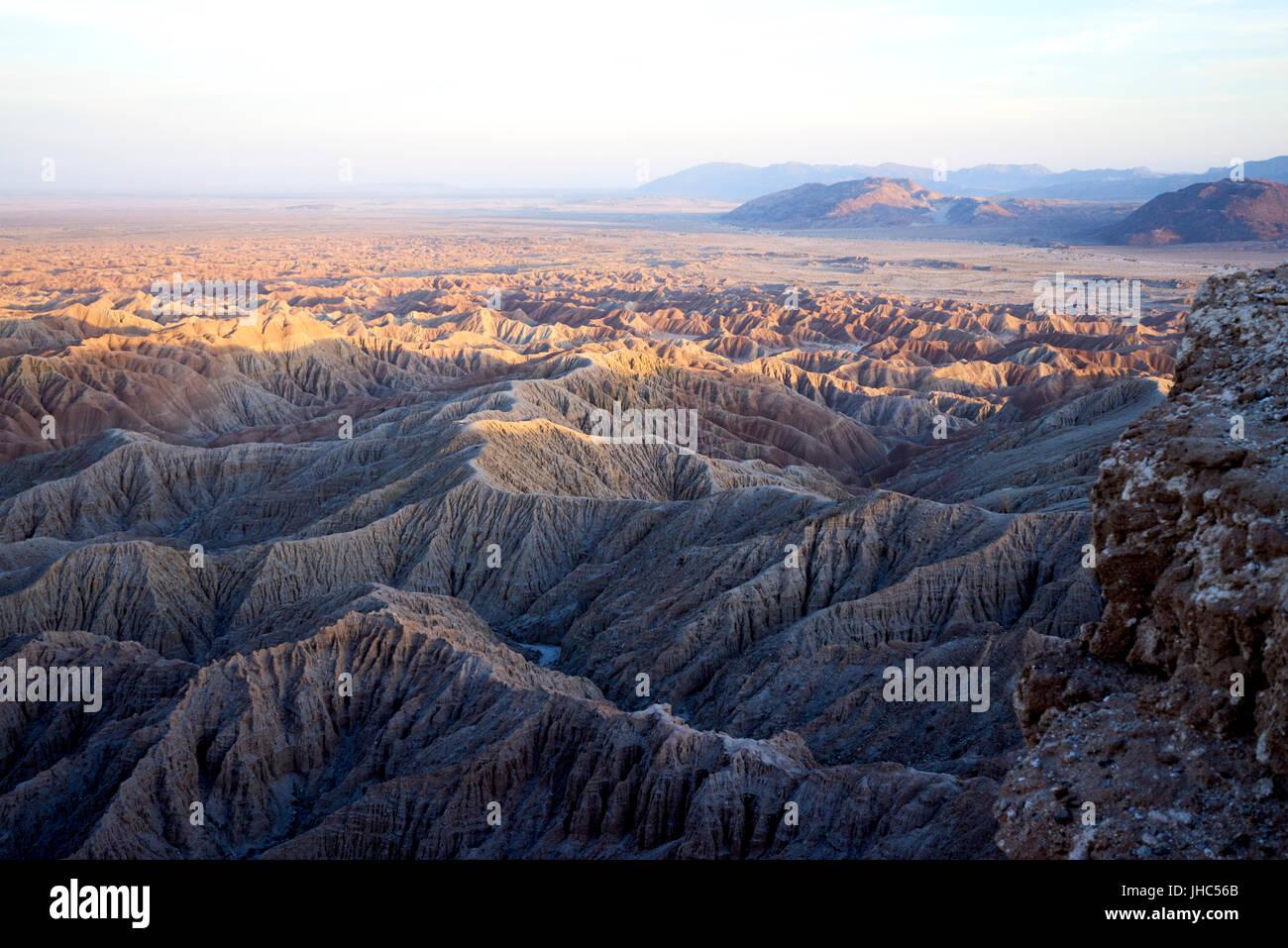 hazy hot vast desert landscape with mountains, ridges, valleys, bathed in evening light - Stock Image