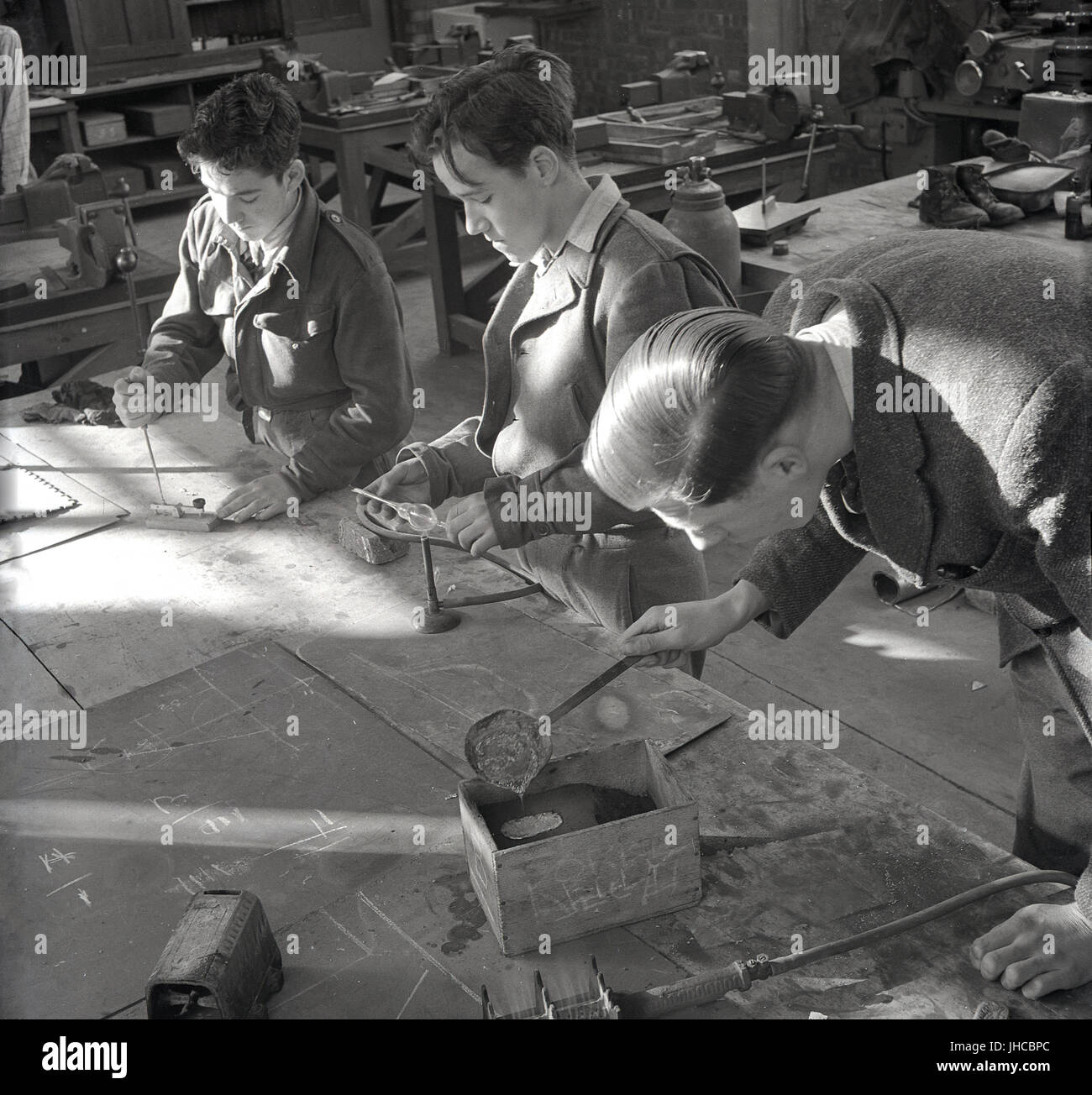 1950s, historical, England, UK, two male students wearing army uniform and teacher doing metal work in a tool shop Stock Photo
