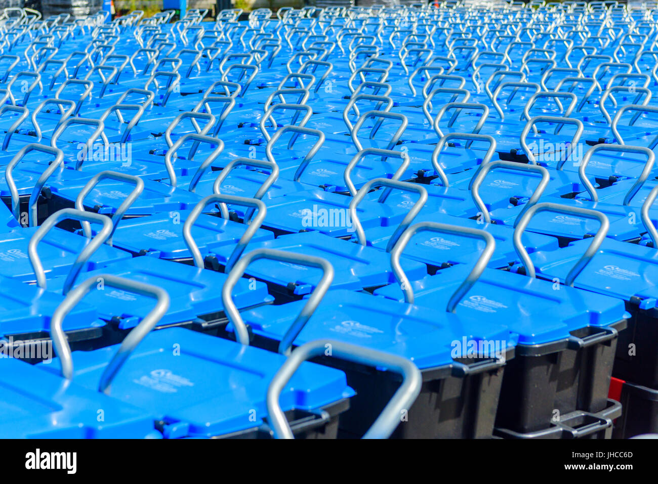 Recycling wheelie bins with three compartments at a council recycling centre, ready to be distributed to local homes. - Stock Image