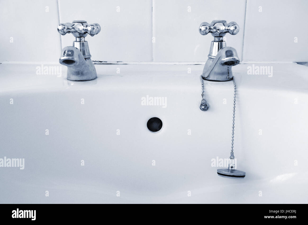 A pair of silver taps on a white sink with a plug on a chain - Stock Image