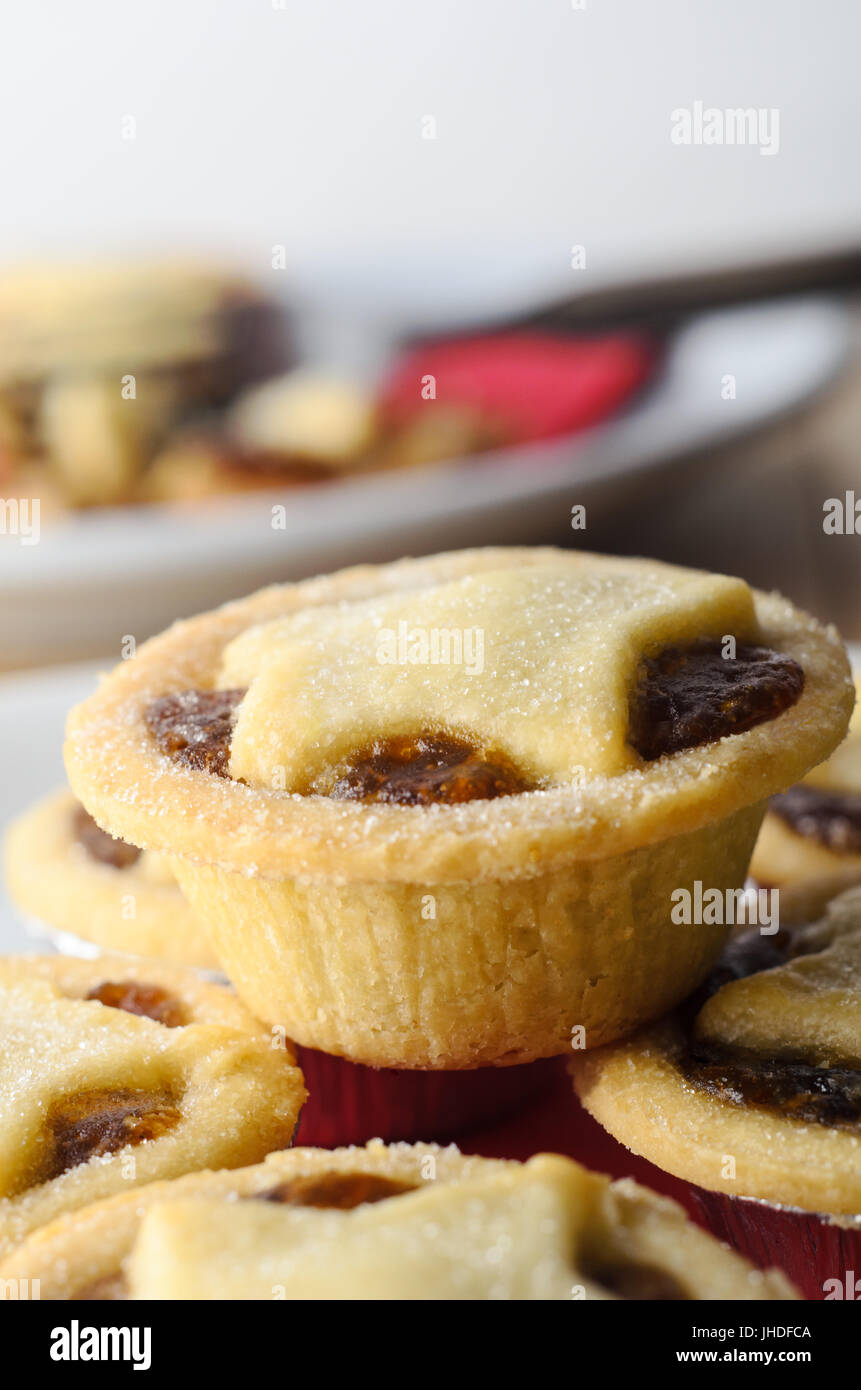 A stack of Christmas mince pies with star shaped pastry toppers in foreground.  A  plate with partly eaten pie, - Stock Image