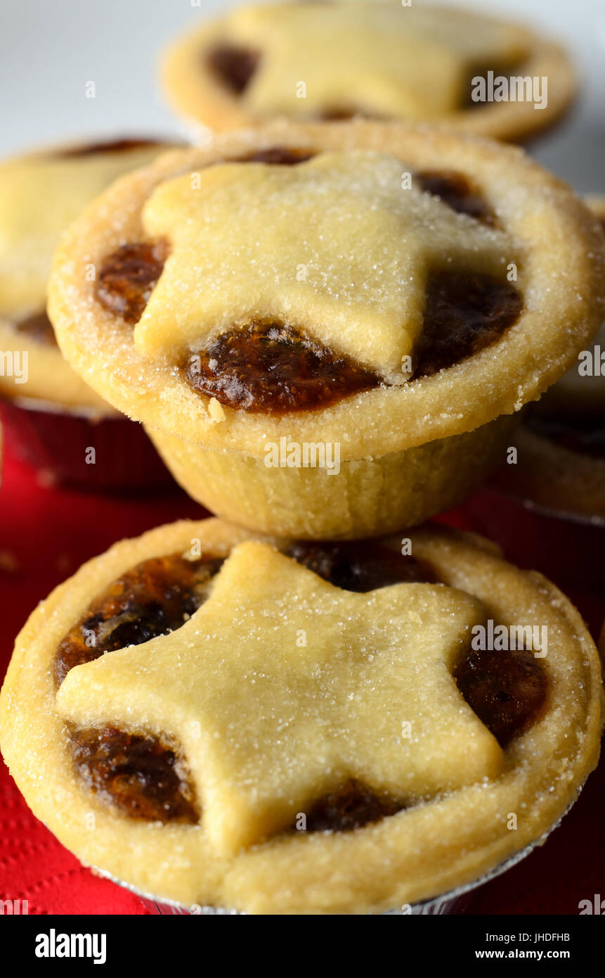 Close up of Christmas mince pies with star shaped pastry toppers, piled on a white plate with crumbs; a red napkin. - Stock Image