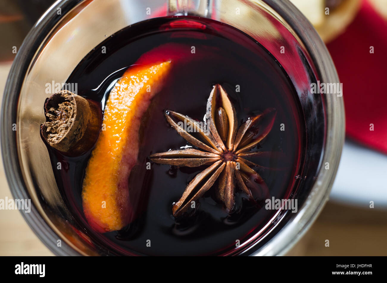Overhead close up (macro) shot of a glass of mulled wine with star anise, orange and cinnamon stick.  Red napkin - Stock Image