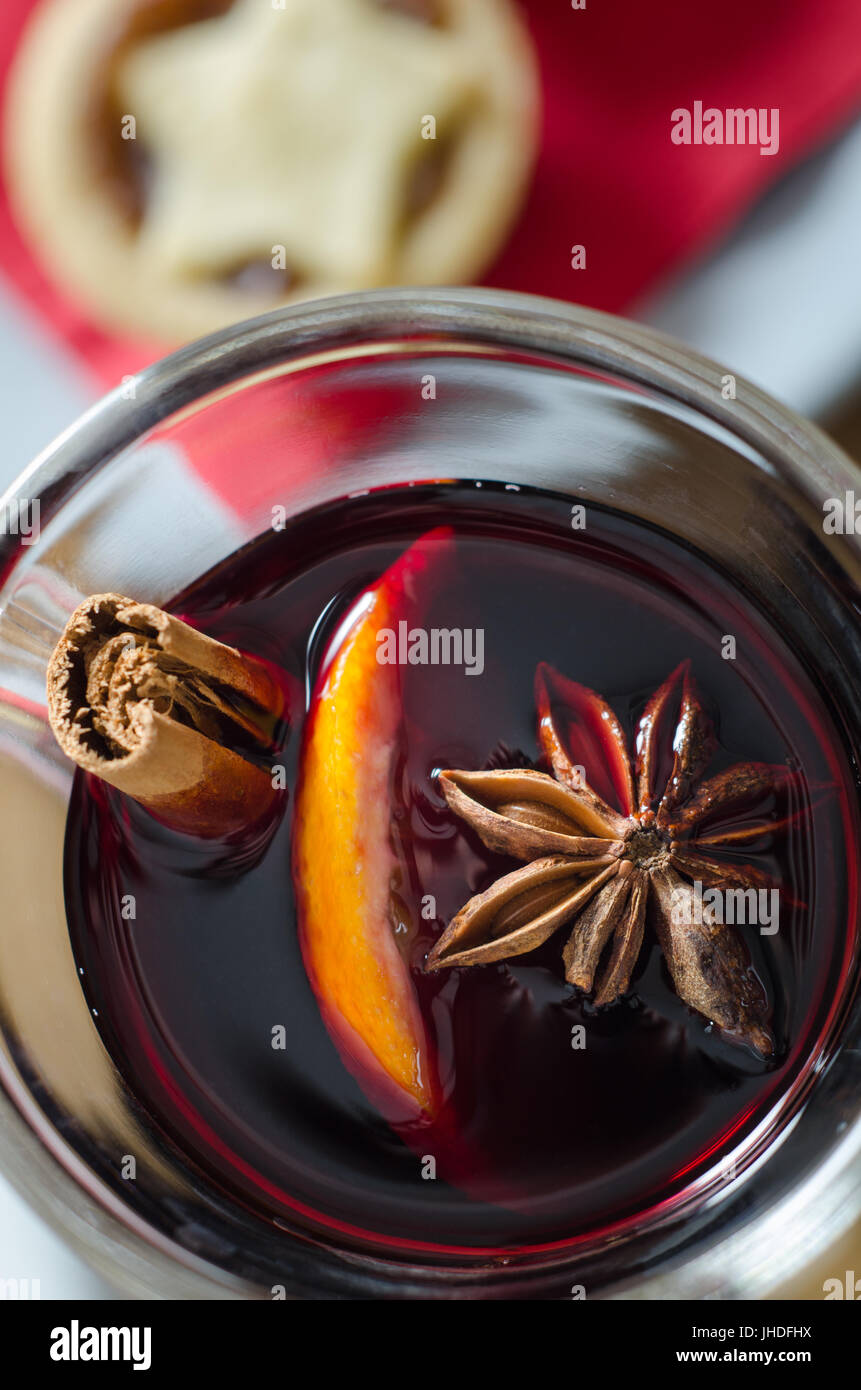 Overhead close up of a glass of spicy mulled wine with star topped Christmas mince pie on red napkin in soft focus - Stock Image