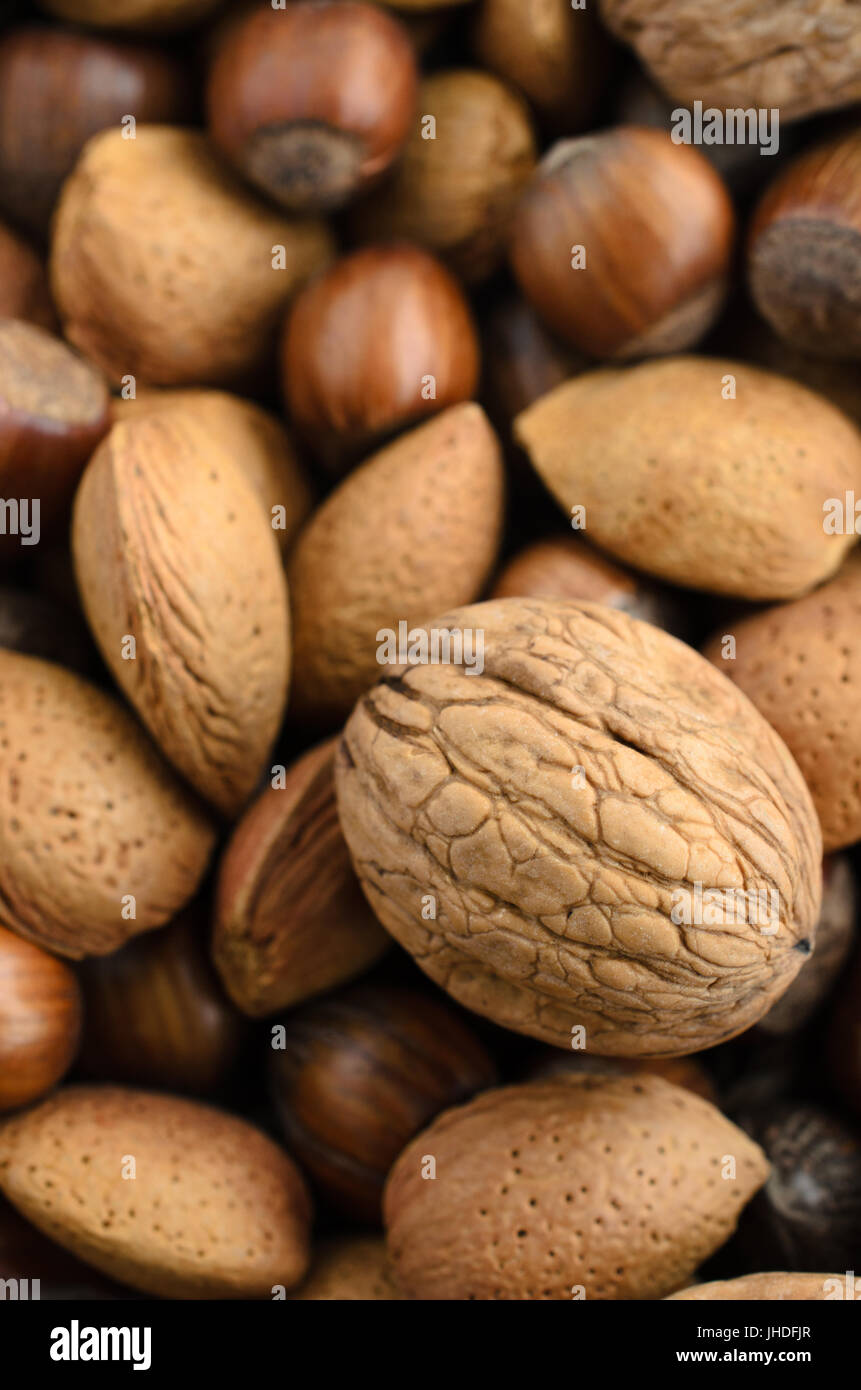 Overhead shot of a selection of mixed nuts, still in their shells. - Stock Image