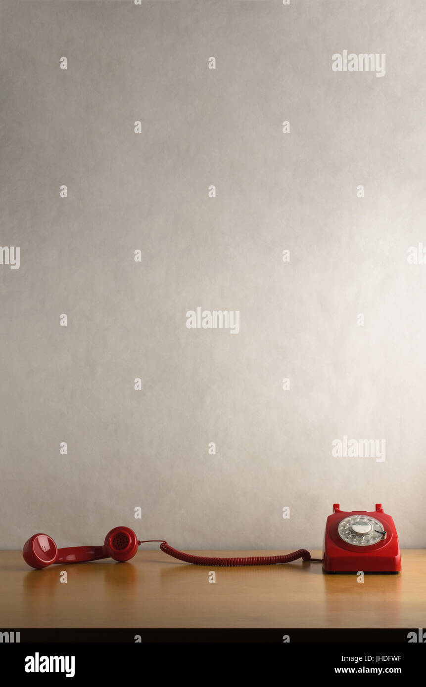 Eye level shot of a retro red dial up telephone on a light wood veneer desk or table with handset taken off the - Stock Image