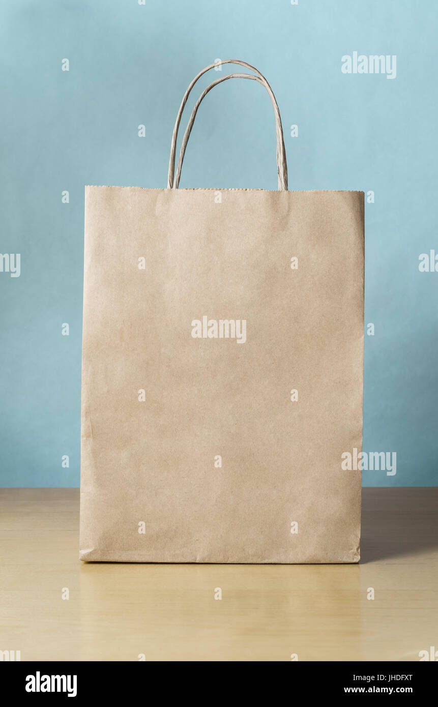 Blank Brown Paper Carrier Bag With Handles For Shopping Facing Front On A Light Wood Veneer Table Pale Blue Wall Background
