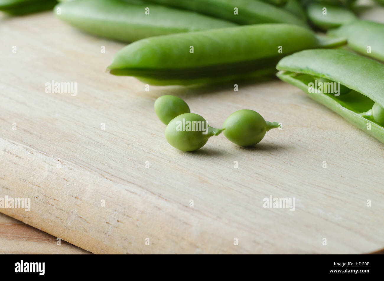 Food preparation scene. Three freshly picked peas with stalks on a wooden chopping board with opened and closed - Stock Image