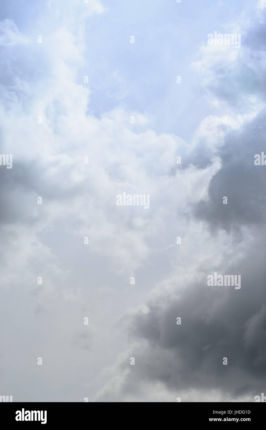 Mystical pale blue sky with light, white and grey fluffy clouds. - Stock Image