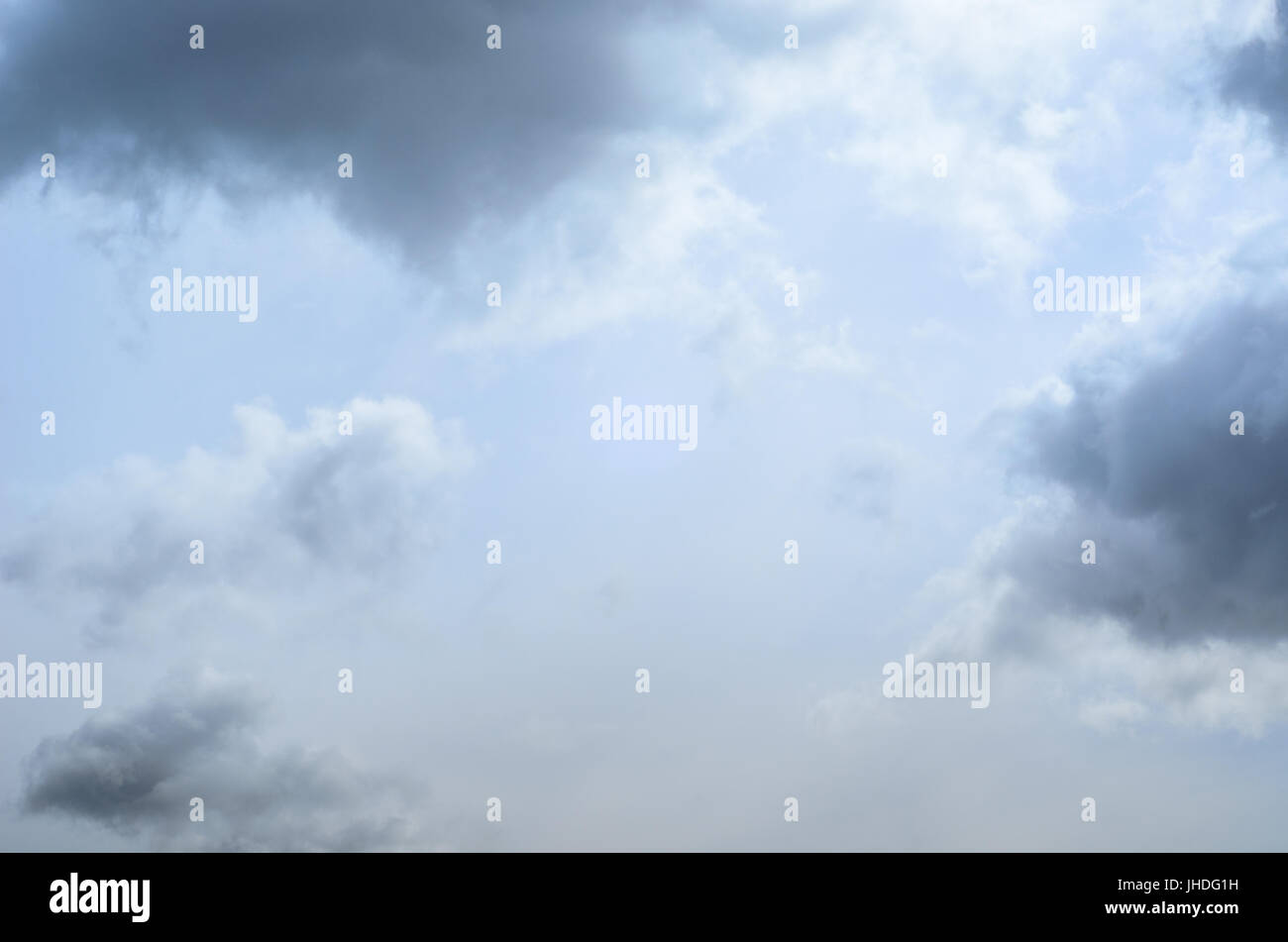 Mystical pale blue sky background with light, white and grey fluffy clouds. - Stock Image