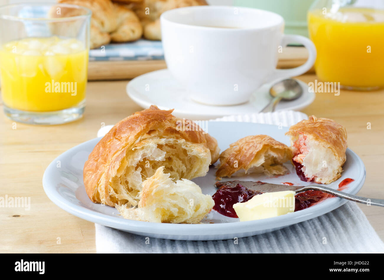 Continental Breakfast table setting laid with croissants orange juice and coffee. A serving of partly eaten croissant with butter and jam is in the f & Continental Breakfast table setting laid with croissants orange ...