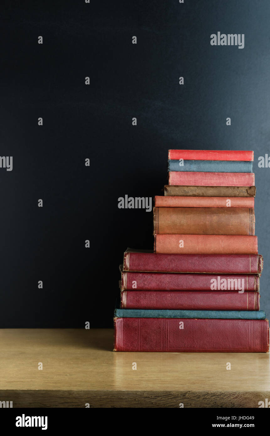 A pile of old, used text books stacked in a pile on a wooden desk in front of a black chalkboard.  Copy space to - Stock Image