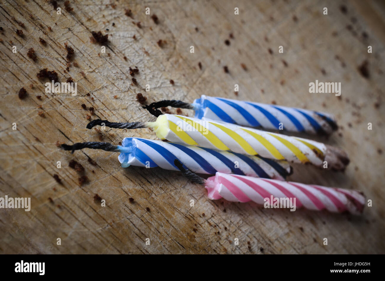 Close up of four used, striped  birthday cake candles, burned out and lying grouped amongst chocolate cake crumbs - Stock Image