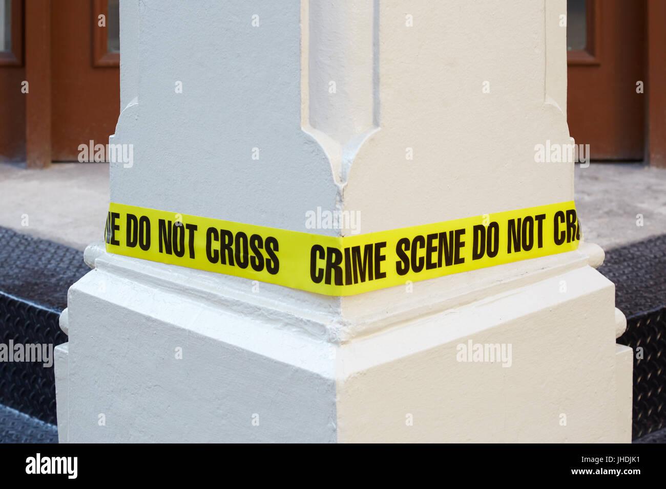 Crime scene do not cross, yellow police tape around a white column - Stock Image