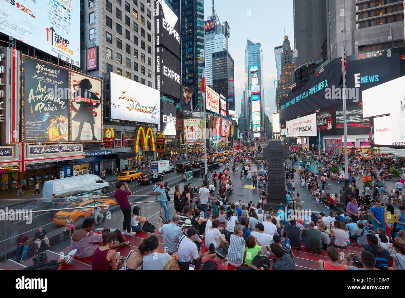 Times Square view with people from tkts bleacher seats in the evening in New York - Stock Image