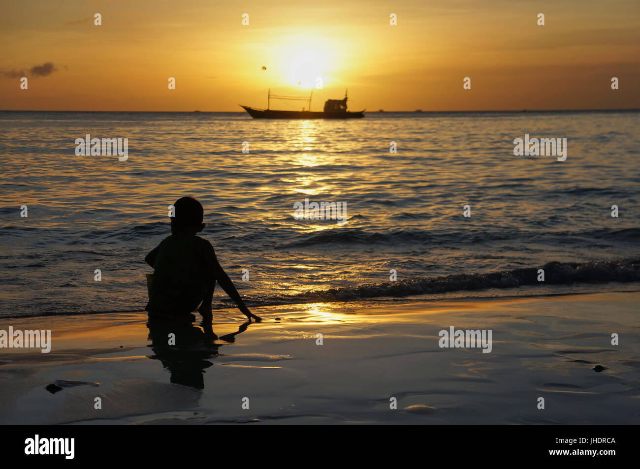 Holiday background. Boy playing against golden sky and sea during sunset. Boy crouched down playing in the sand - Stock Image