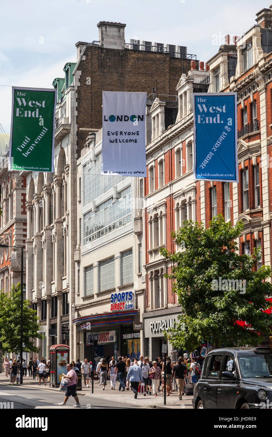 Crowds of pedestrians, locals and visitors in Oxford Street in London's West End under welcoming banners with - Stock Image