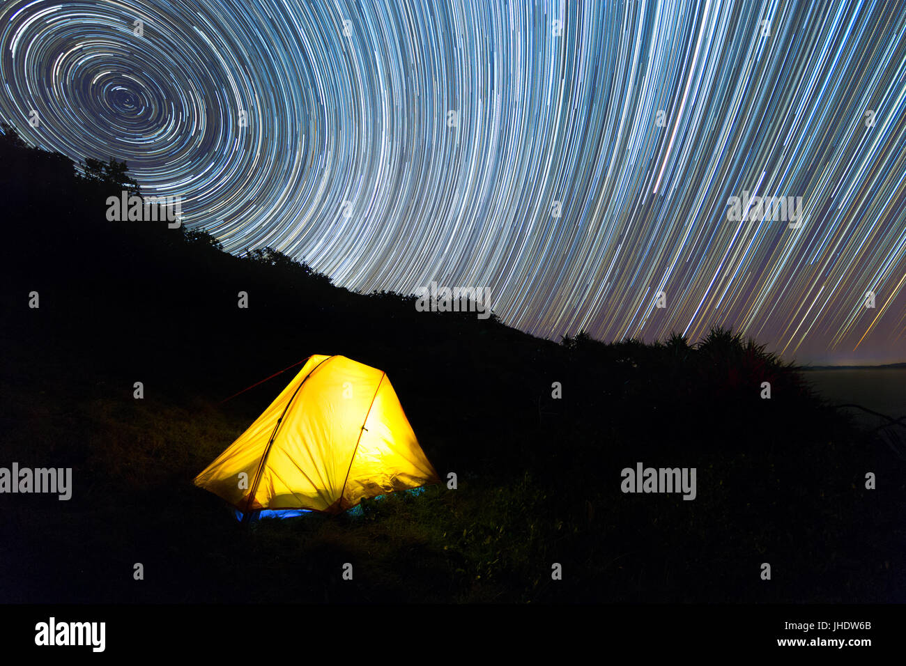 A yellow hiking tent illuminated with light under a beautiful night sky star trail. Stock Photo